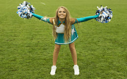 Cheerleader girl with poms on field Stock Photo