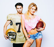 Cheerleader Girl and quarterback young man fans of American football are posing in uniform with a ball and helmet. Super. Cheerleader Girl and quarterback young Royalty Free Stock Photography