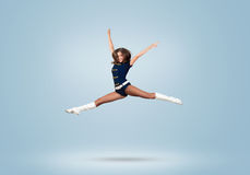 Cheerleader girl. Young beautiful smiling cheerleader girl jumping high stock images