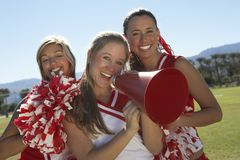 Cheerleader Holding Megaphone. Portrait of happy cheerleader holding megaphone with friends Stock Photography