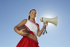 Cheerleader Holding Rugby Ball And Megaphone. Low angle view of happy cheerleader holding rugby ball and megaphone against clear sky Royalty Free Stock Images