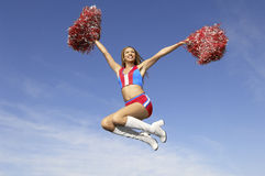 Cheerleader Jumping Midair With Pom Poms. Low angle view of a cheerful cheerleader jumping midair with pom poms against the sky royalty free stock photo