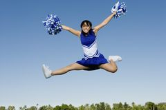 Cheerleader Jumping With Pom-Poms royalty free stock images