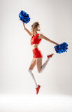 Cheerleader jumping with pom-poms royalty free stock image