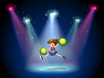 A cheerleader jumping on the stage with spotlights Stock Photo