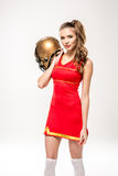 Cheerleader posing with helmet Stock Images