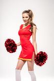 Cheerleader posing with pom-poms Royalty Free Stock Images