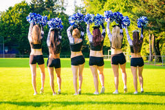 Cheerleader Team Practicing. Cheerleaders practicing on playing field on a summer day Stock Photos