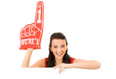 Cheerleader: Wearing a Foam Finger. Cute female as an American sports cheerleader, in red and white outfit.  Isolated on white background Royalty Free Stock Images