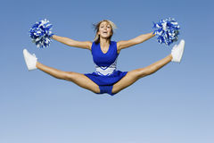 Cheerleader With Pompoms Doing Splits Against Sky Royalty Free Stock Image