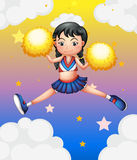 A cheerleader with yellow pompoms Royalty Free Stock Photos