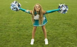 Cheerleadermädchen mit poms auf Feld Stockfoto