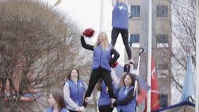 Cheerleadern in den Jacken machen akrobatische Elemente auf Stadium Rote Schüttele-Apparat outdoor stock video footage