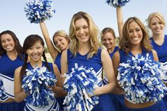 Cheerleadern, die Pom-Poms halten Lizenzfreie Stockfotografie