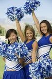 Cheerleadern, die Pom-poms wellenartig bewegen Lizenzfreies Stockfoto