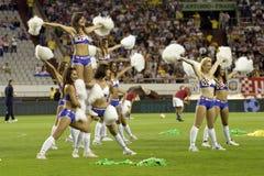Cheerleadern, die während des Fußballspiels durchführen stockfotografie