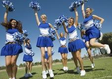Cheerleadern mit Pompoms zujubelnd auf Feld Stockfotografie