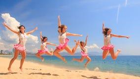 Cheerleadern tanzen untersetzte Showhaltungen auf Strand gegen Meer