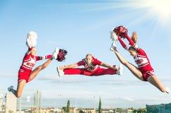 Cheerleadern team, einen Sprung mit männlichem Trainer durchführend Stockbild