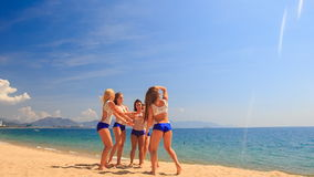 Cheerleaders from backside perform Back Tuck Basket Toss on sand stock footage