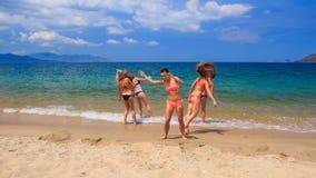 Cheerleaders in bikinis perform hand scale stunt on wet sand stock video footage