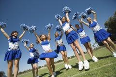 Cheerleaders Cheering On Field. Group of excited young cheerleaders cheering on field Stock Photo