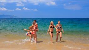 Cheerleaders in colourful bikinis jump gambol in water stock footage