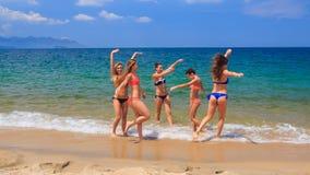 Cheerleaders in colourful bikinis jump wave hands in water stock footage