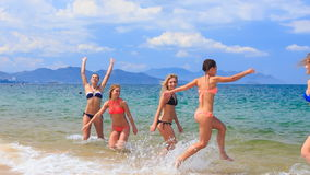 Cheerleaders in colourful bikinis run into water splash stock footage