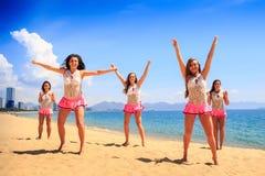 Cheerleaders dance differently on beach against azure sea Stock Photos