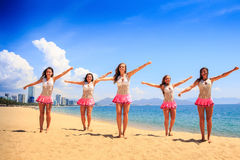 Cheerleaders in dance pose bent arms on beach against sea Stock Image