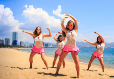 Cheerleaders in dance pose hands over head on beach against sea Stock Image