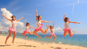 Cheerleaders dance squat show poses on beach against sea. Cheerleaders in white pink uniform squat dance and show different poses on sand beach against sea wind