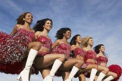 Cheerleaders die Hoge Schop doen tegen Bewolkte Hemel Royalty-vrije Stock Foto's