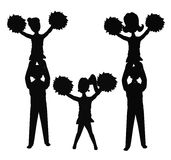 Cheerleaders in formation in silhouette. Cheerleaders in silhouette in formation with girls standing on boys shoulders Royalty Free Stock Photos
