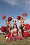 Cheerleaders In Group Cheering. Group of multiethnic cheerleaders cheering in red uniform with pompoms on field Stock Photos