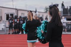 Cheerleaders at high school football game. Cheerleaders welcoming the players at a high school football game royalty free stock photography