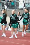 Cheerleaders At A High School Football Game. A group of cheerleaders at a high school football game stock photo