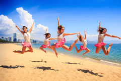 Cheerleaders jump in Scales at once on beach against sea Stock Image
