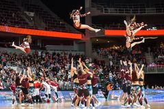 Cheerleaders jumping in the air, during performance at half time. Basketball game. royalty free stock image