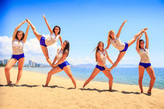 Cheerleaders perform double Heel Stretch on sand against sea Royalty Free Stock Photos