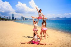 Cheerleaders perform High Straddle Stunt on beach against sea Stock Images