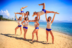 Cheerleaders perform sideview Swedish falls on beach against sea Stock Photo