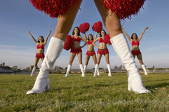 Cheerleaders Performing On Field. Multiethnic cheerleaders with pom poms performing on field Stock Photography