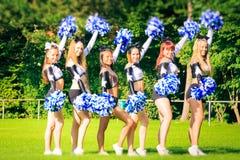 Cheerleaders Practicing Outdoors. Photo of cheerleaders practicing on playing field Stock Photo
