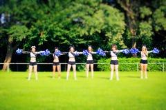 Cheerleaders Practicing Outdoors. Photo of cheerleaders practicing on playing field Royalty Free Stock Photos