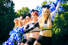 Cheerleaders Practicing Outdoors. Photo of cheerleaders practicing on playing field Stock Photography