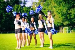 Cheerleaders Practicing Outdoors. Photo of cheerleaders practicing on playing field Royalty Free Stock Image