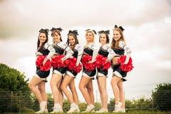 Cheerleaders Rooting For Their Team. Outdoors shot of cheerleaders rooting for their team Stock Images