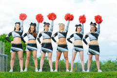 Cheerleaders Rooting For Their Team. Outdoors shot of cheerleaders rooting for their team Royalty Free Stock Photo